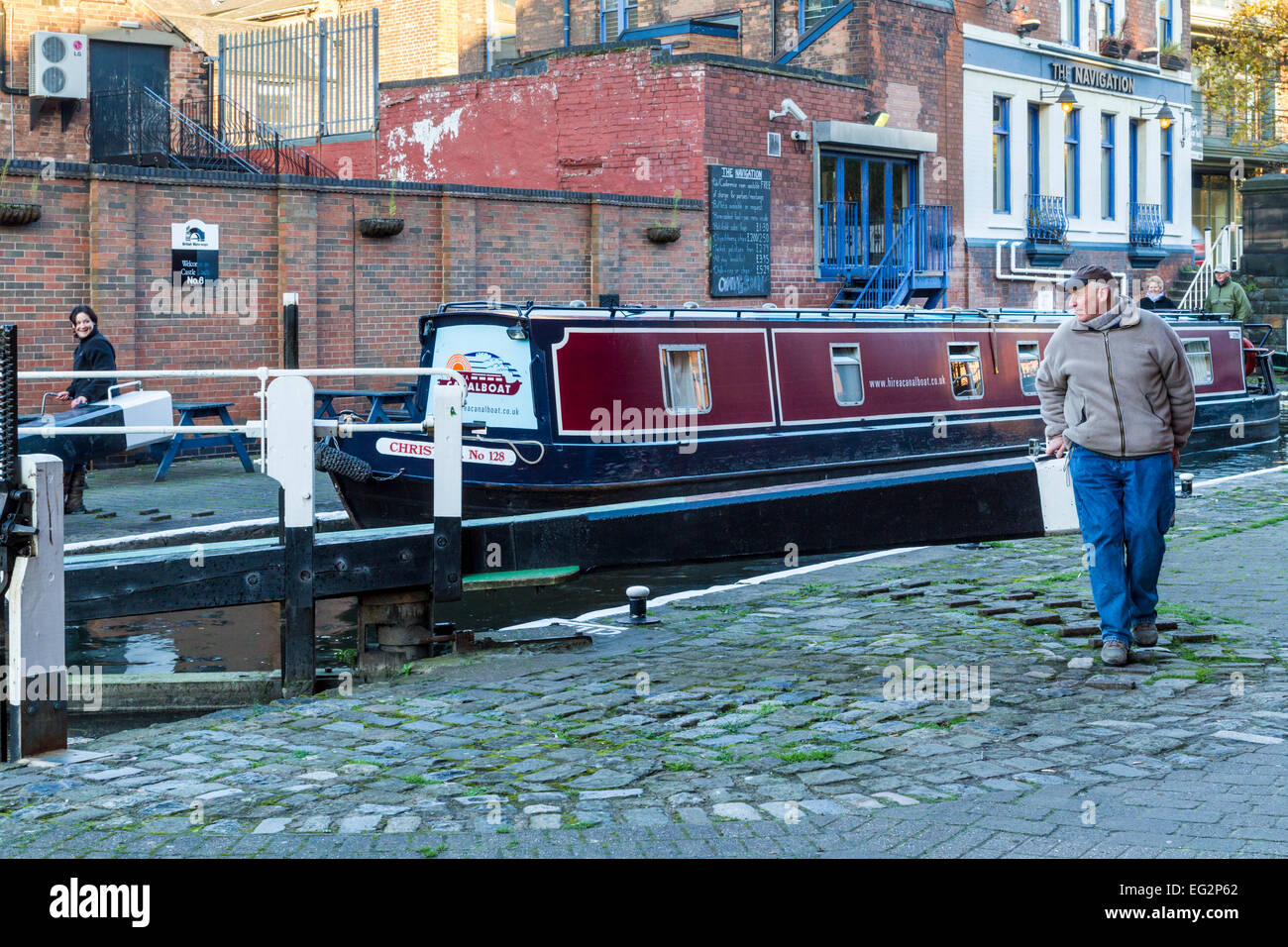 Man and woman opening lock gates on the Nottingham and Beeston Canal with the Navigation pub behind. Nottingham, - Stock Image