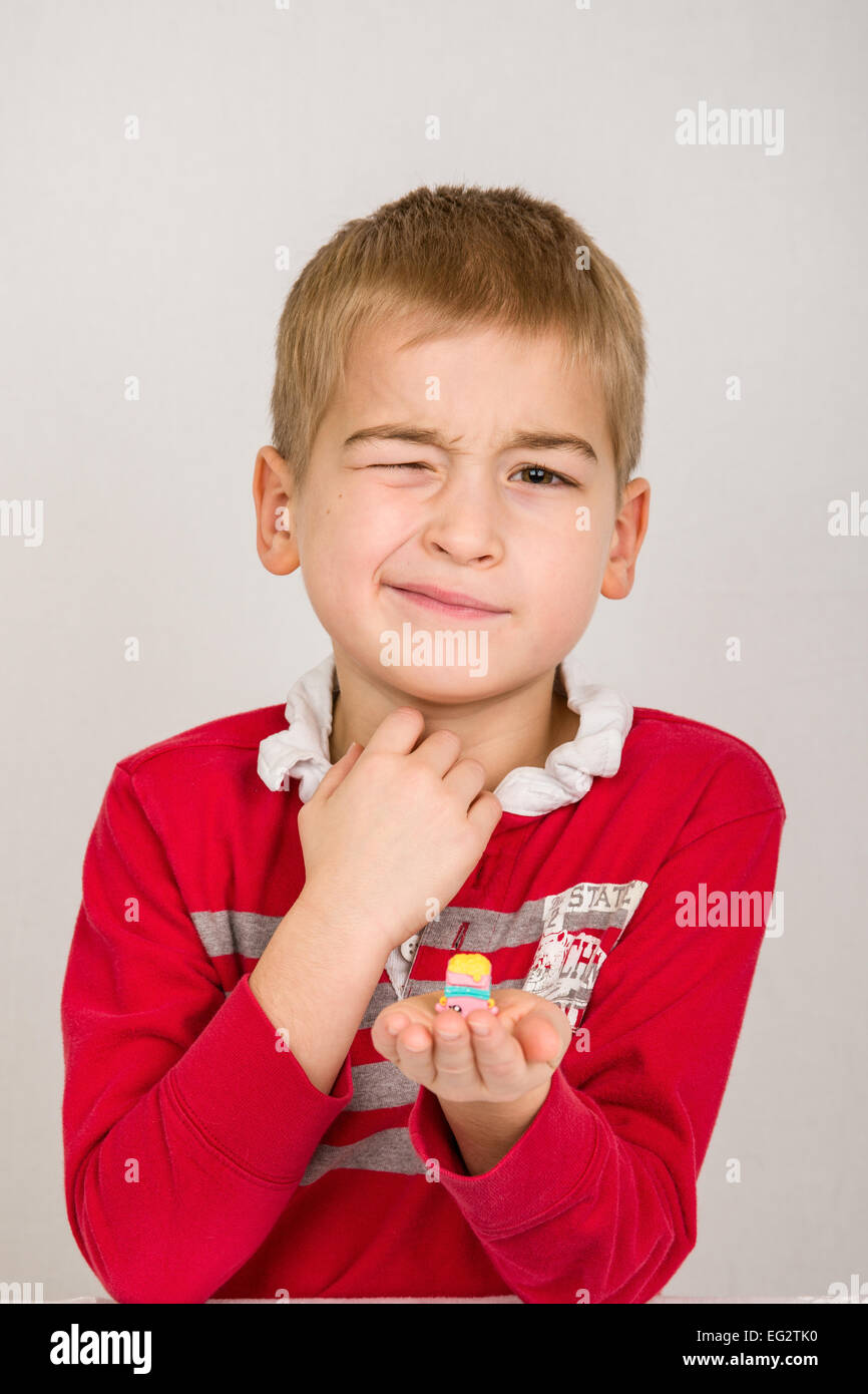 Six year old boy struggling to wink, imitating his Shopkins toy which is winking - Stock Image