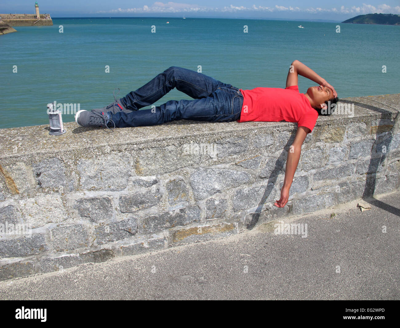 Binic, boy sleeping at harbour,Cotes-d'Armor,Bretagne,Brittany,France - Stock Image