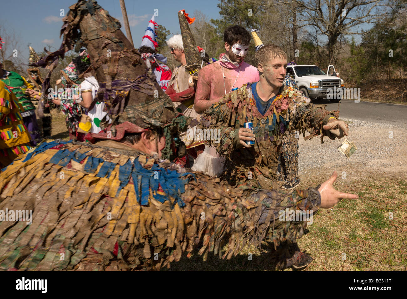 Revelers chase a dollar bill during the traditional Cajun Courir de Mardi Gras February 14, 2015 in Elton, Louisiana. - Stock Image