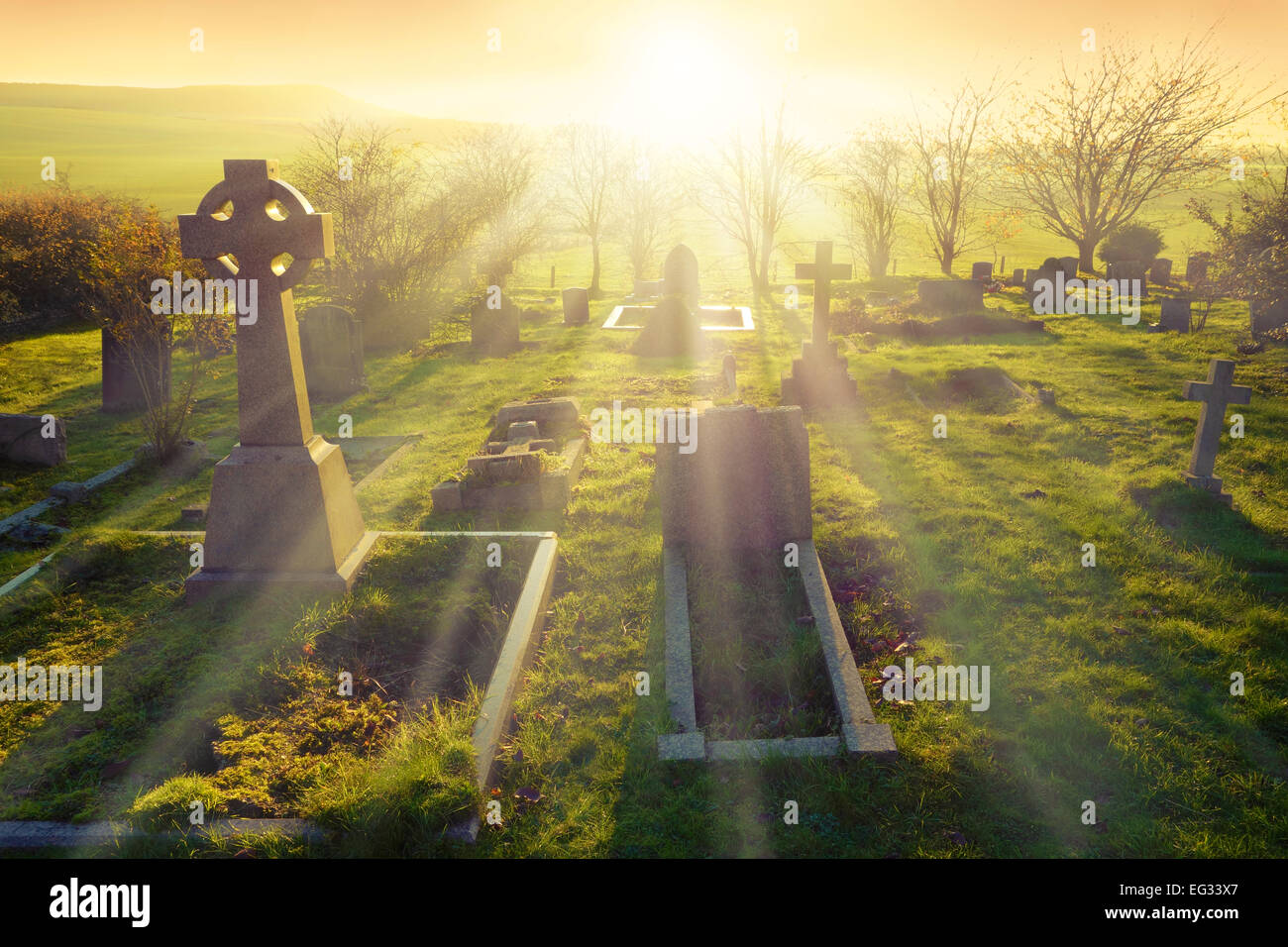 Heavenly light shining upon a old graveyard in England, United Kingdom. - Stock Image