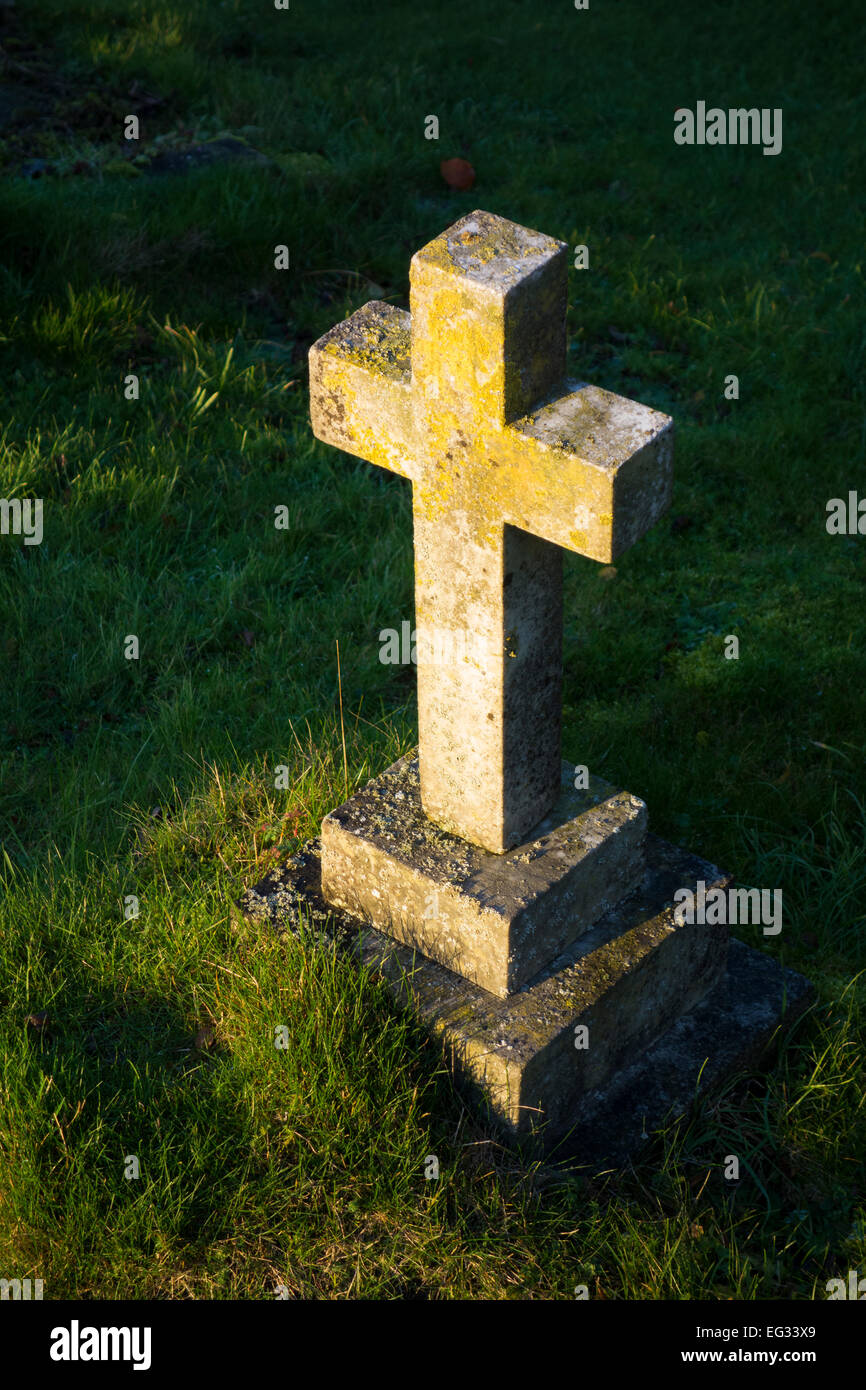 The golden light of the setting sun shining upon a gravestone cross in a cemetery in England, United Kingdom - Stock Image