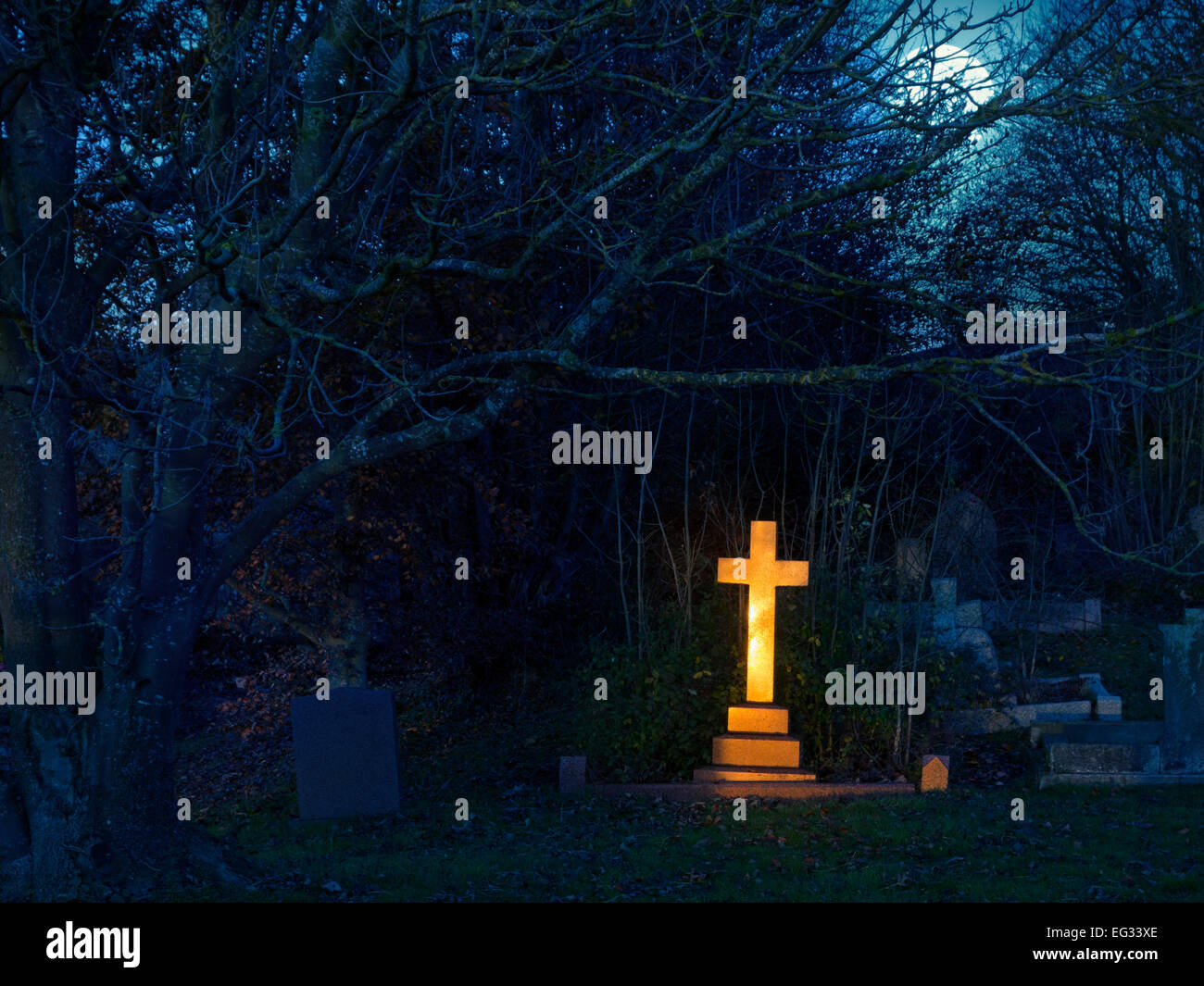 Golden light  shining upon a gravestone cross in a cemetery in England, United Kingdom - Stock Image