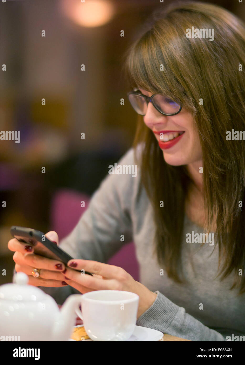 Beautiful young woman checking her mobile phone whilst having a hot drink a cosy cafe. - Stock Image