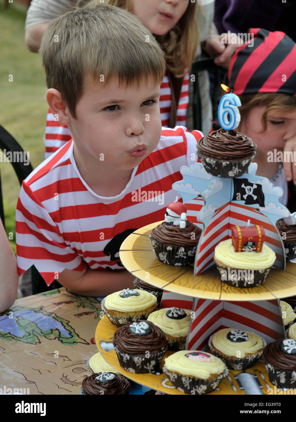 Boy Blowing Out Candles On Cake At Outdoor Pirate Birthday Party