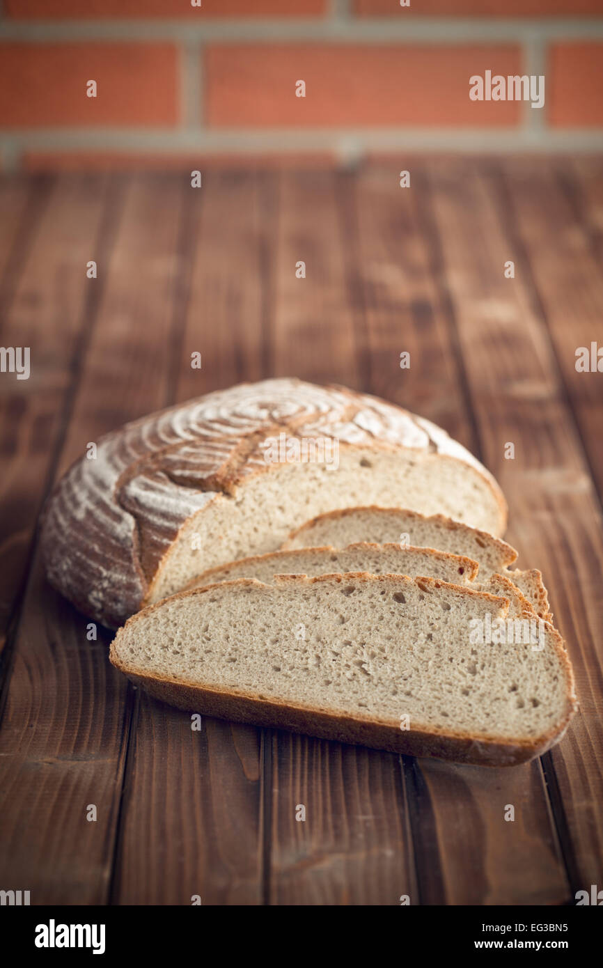 sliced bread on wooden table - Stock Image