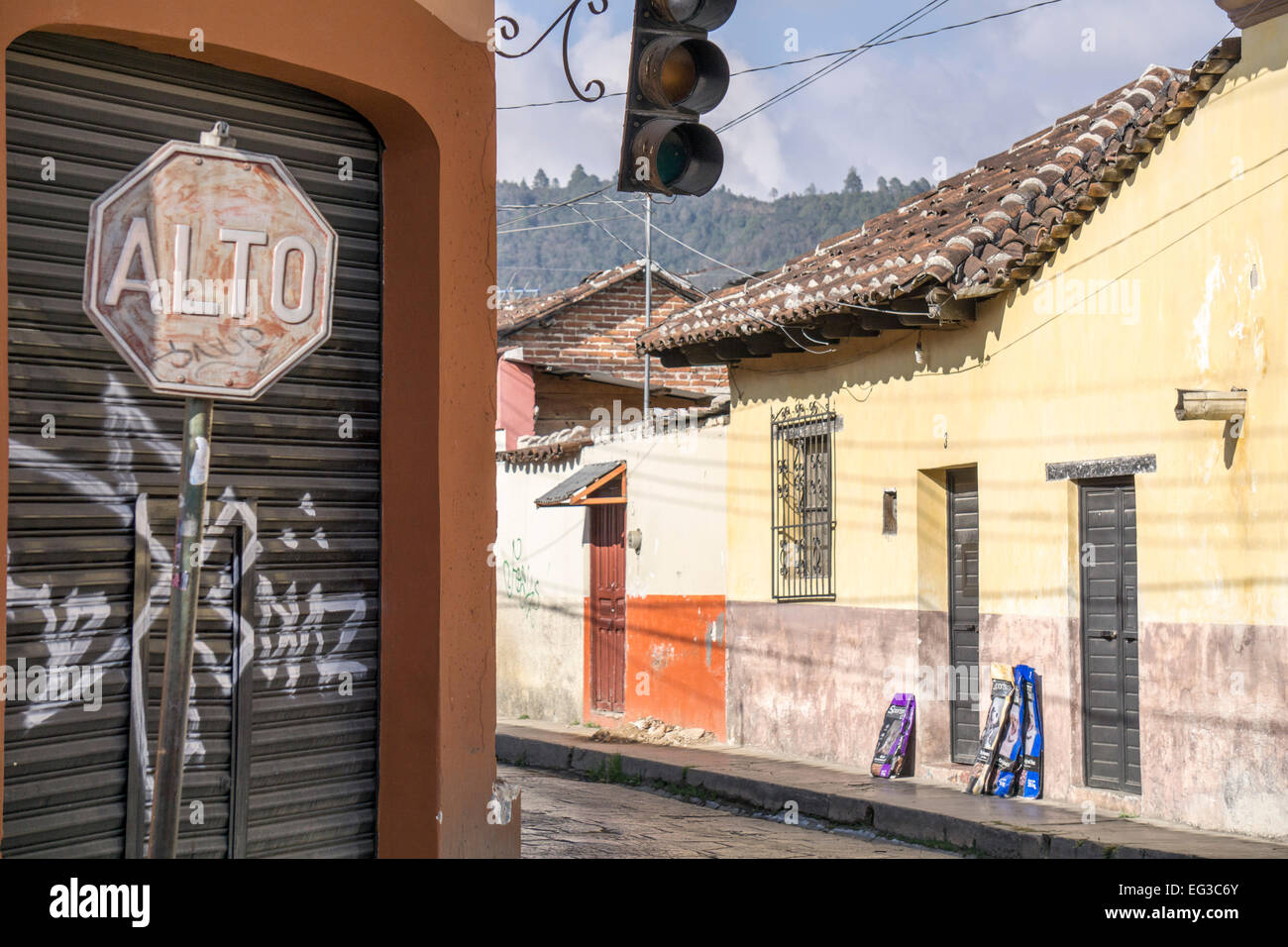 streetcorner in San Cristobal de las Casas with faded old stop sign non functioning traffic light and view of houses - Stock Image