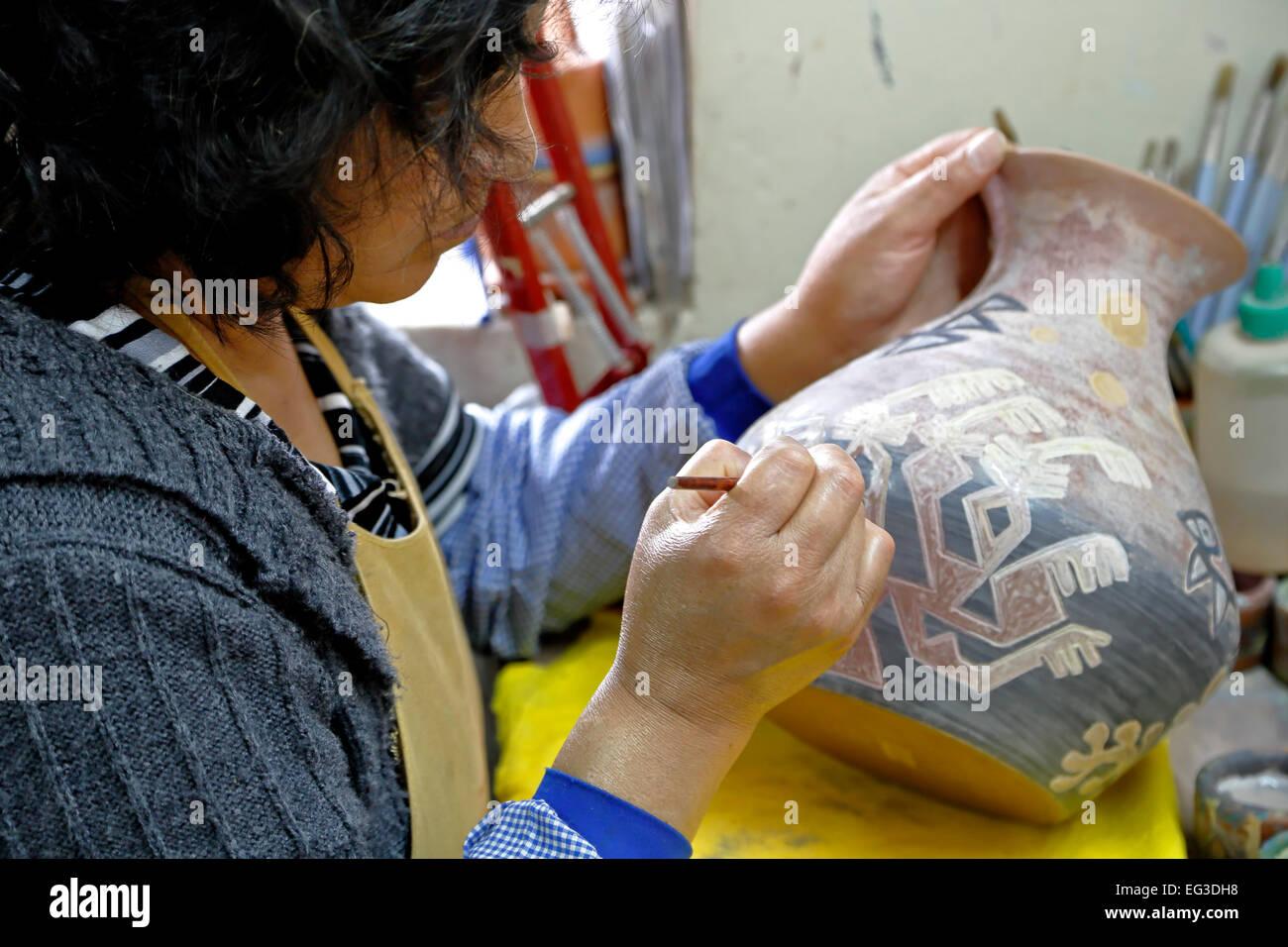 Woman artisan painting ceramic pot, Seminario Ceramics, Urubamba, Cusco, Peru - Stock Image