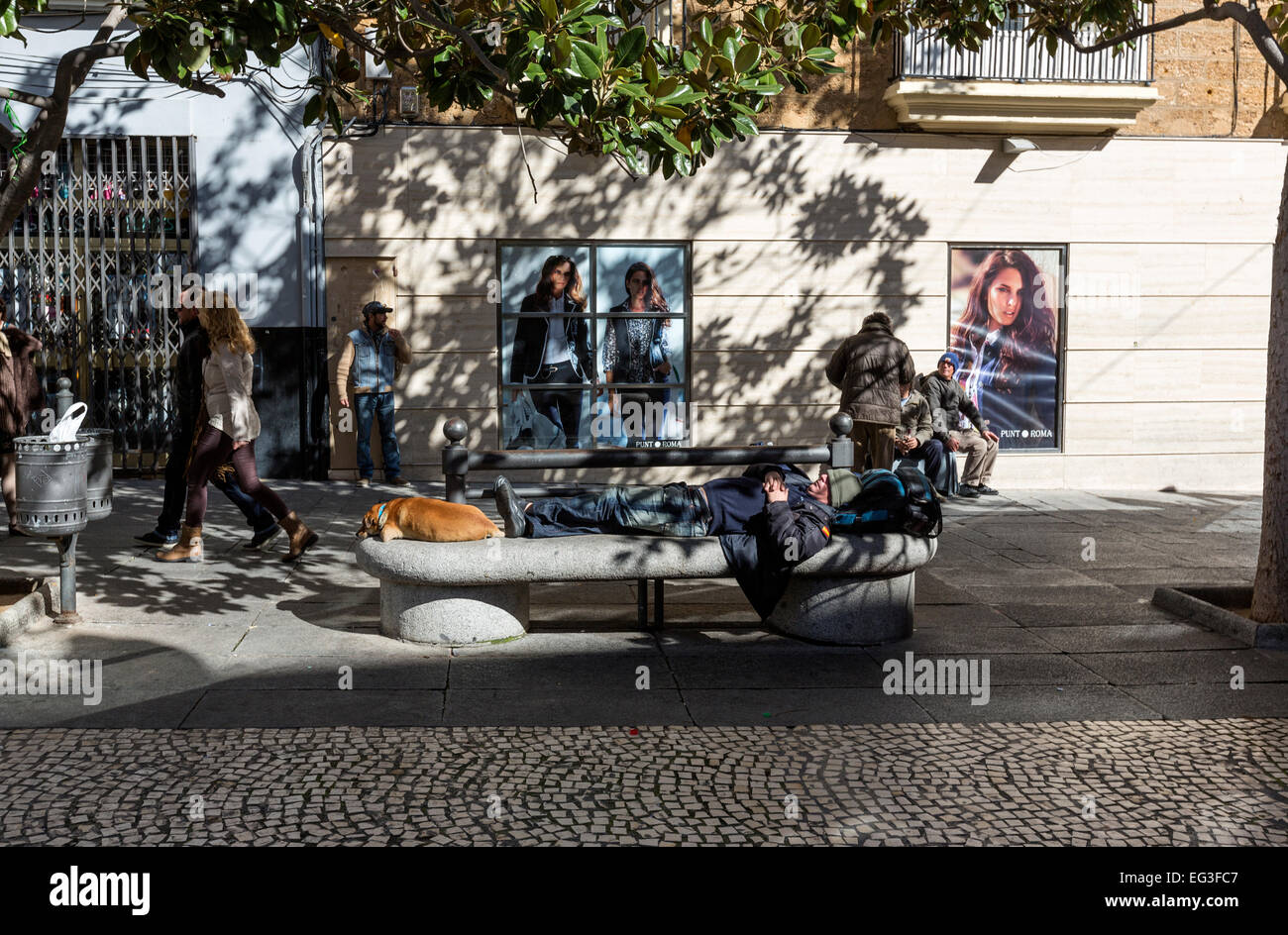 Man having a siesta with his dog in a bank in Cadiz - Stock Image