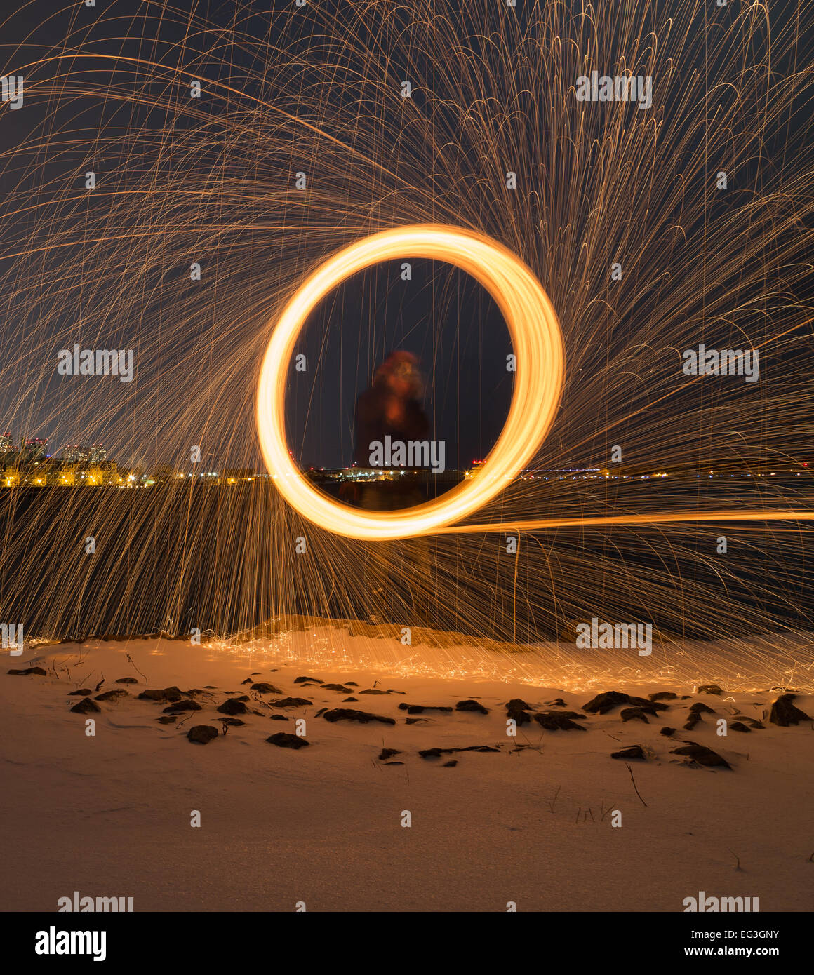 A man spinning wool outside at night with copyspace at the bottom Stock Photo