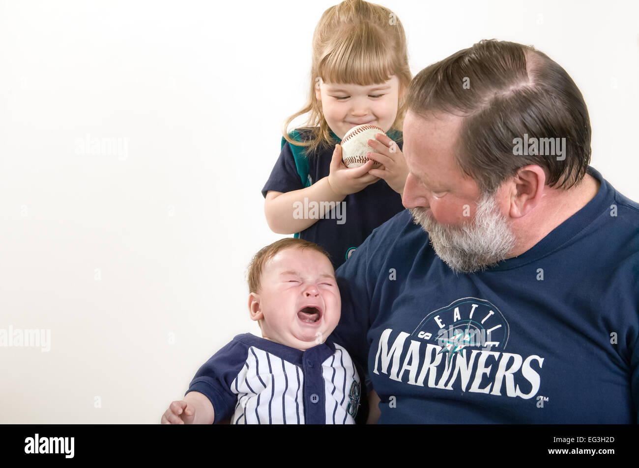 Sixty-one year old grandfather holding three month old grandson, with two year old, impish granddaughter looking - Stock Image