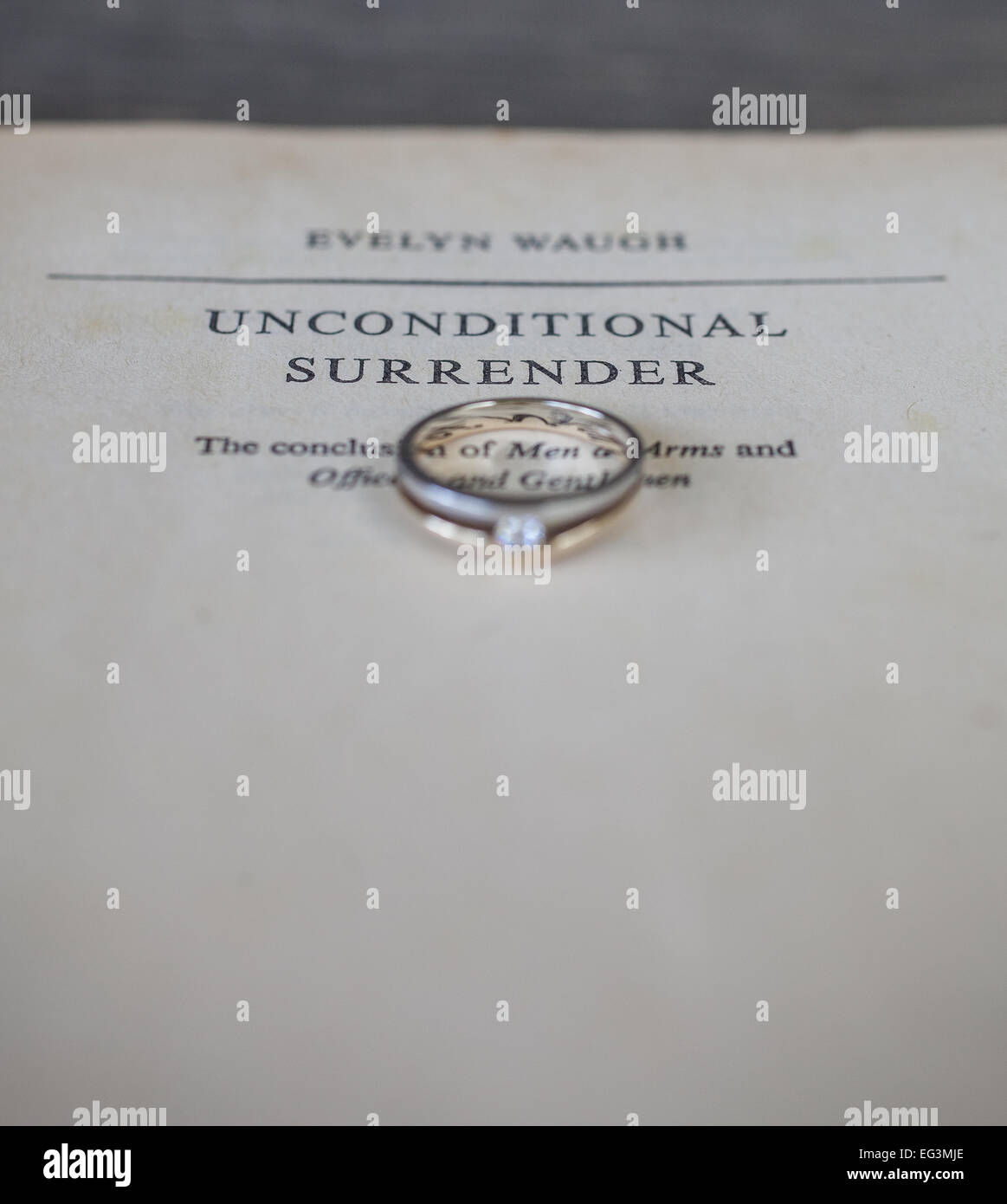 Wedding ring placed on the title page of a novel - Stock Image