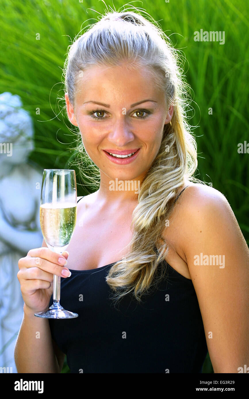 Frau in Partykleid trinkt ein Glas Champagner Sekt (Modellfreigabe ...