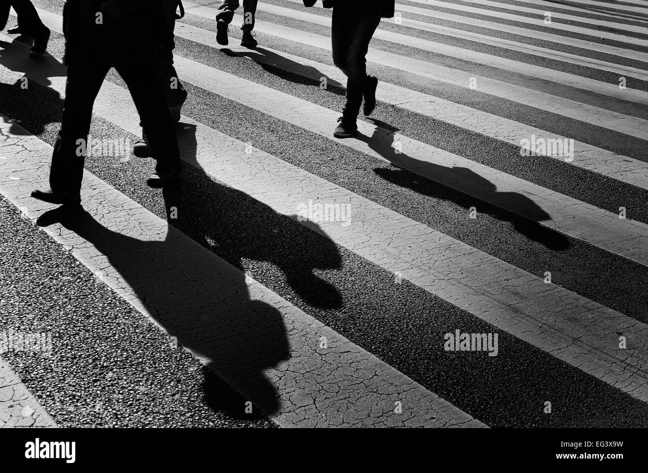 black and white photograph of people and shadows walking on a city street crossing, Budapest Hungary. - Stock Image