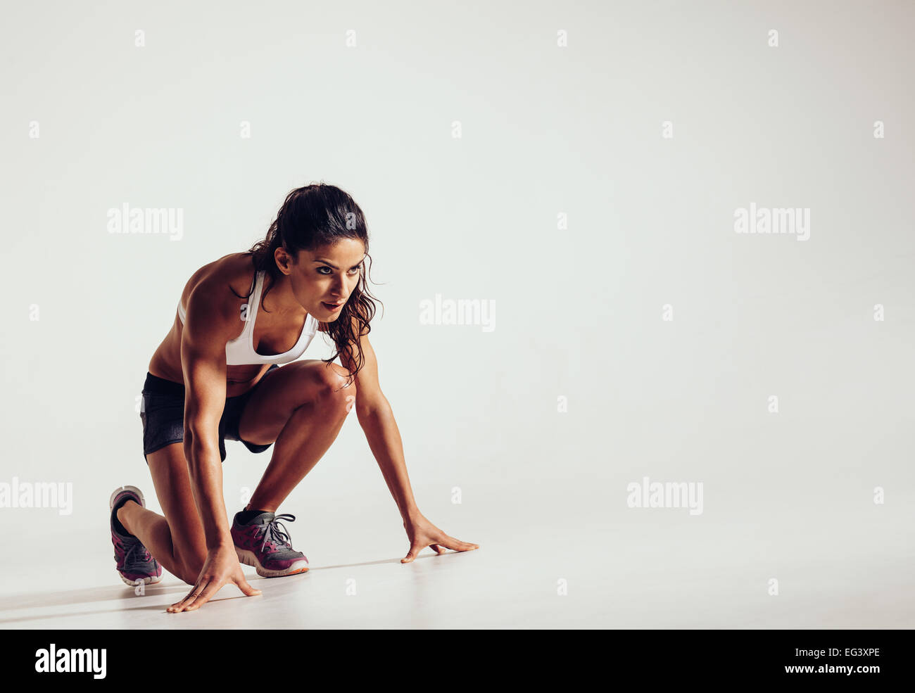 Female athlete in position ready to run over grey background. Determined young woman ready for a sprint. Stock Photo