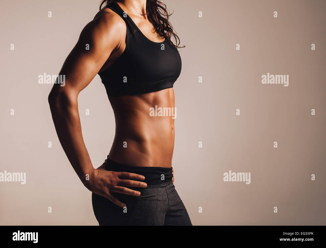 Cropped shot of fit woman's torso with her hands on hips. Female with perfect abdomen muscles. - Stock Image