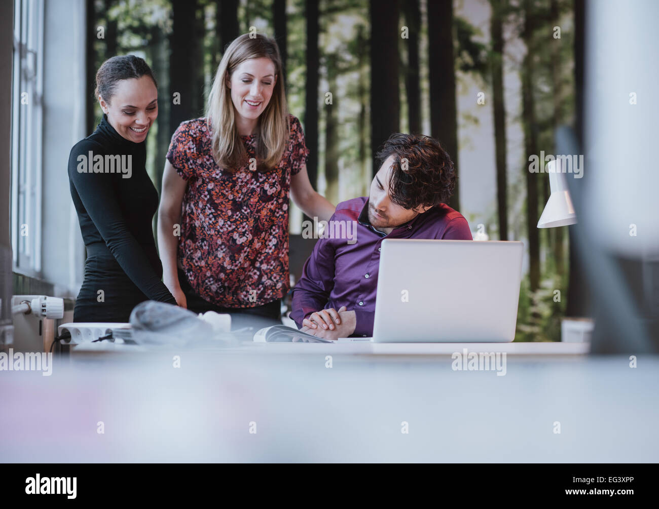 Team of young professionals looking at a catalogue and smiling. Creative team together viewing at a book on desk. - Stock Image