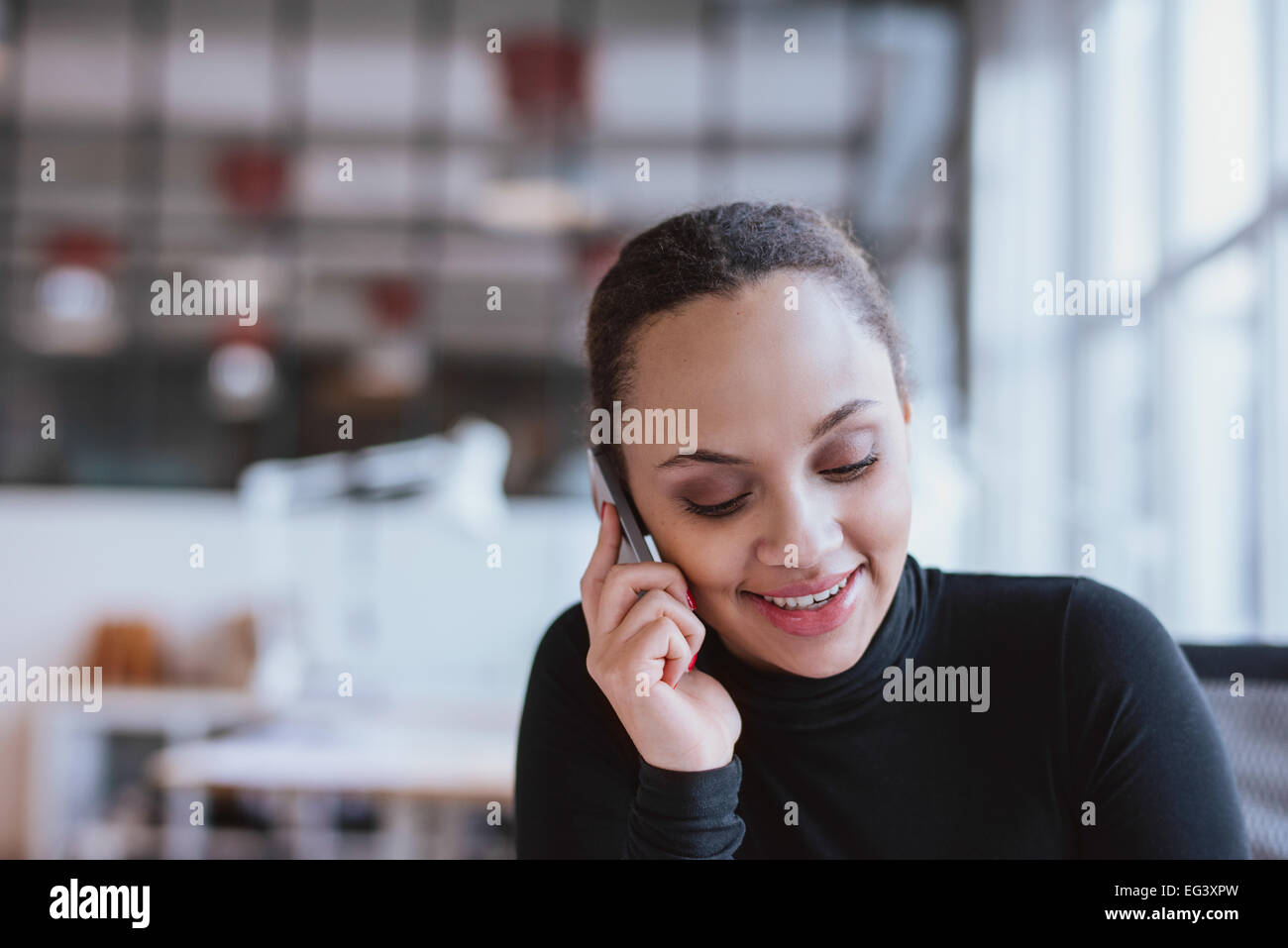 Closeup image of young woman talking on mobile phone. African american female model using cell phone at work. - Stock Image