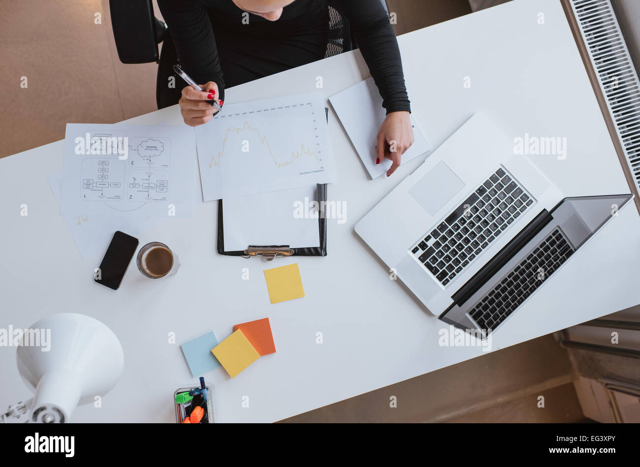 Top view of woman executive working at her desk with chart and laptop. Reviewing financial data and plotting progress - Stock Image