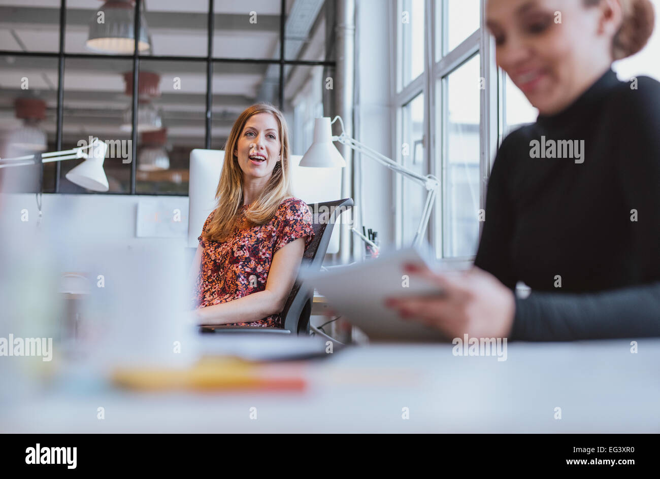 Happy young woman having a friendly chat with her female colleague while at work - Stock Image