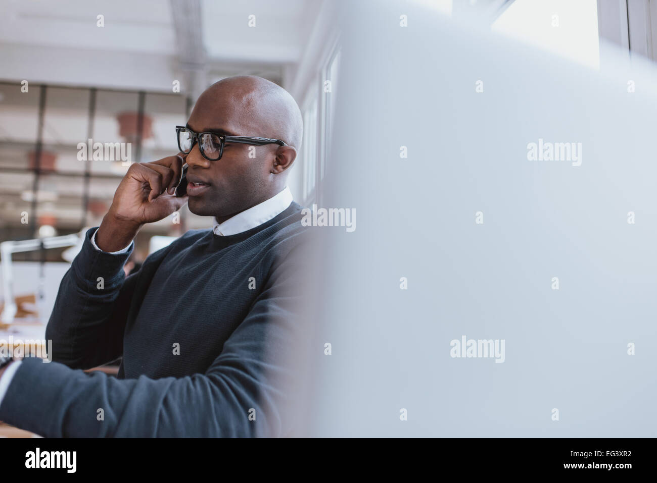 Shot of a young businessman talking on cellphone while at work. Bald african executive in conversation with client - Stock Image