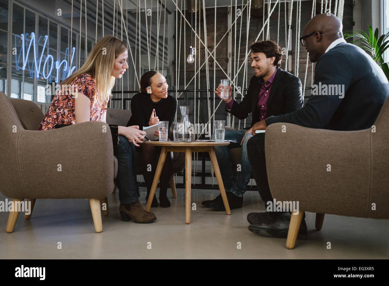 Multiracial business team sitting in office lobby discussing new business ideas. Young man drinking water. Happy - Stock Image