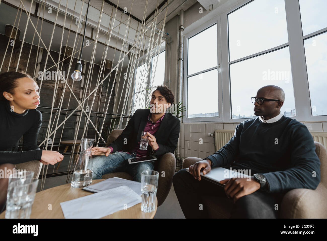 Group of multi ethnic executives discussing during a meeting in office lobby. Business people brainstorming ideas. - Stock Image