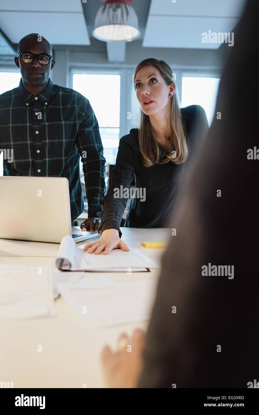 Businesswoman working on new ideas. Young woman showing new business proposal to coworkers during a meeting in office - Stock Image