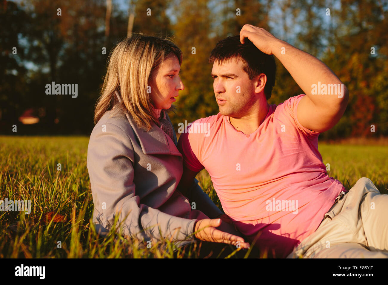Young couple sitting on a meadow - Stock Image