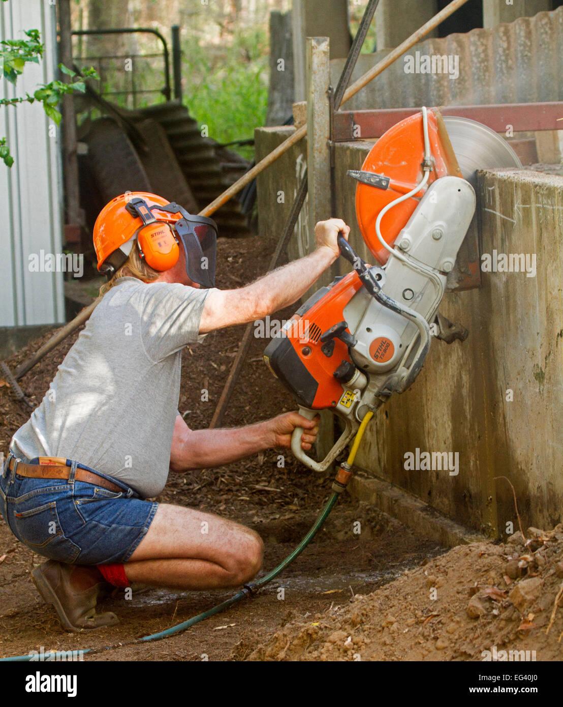 Man Wearing Ear Amp Eye Protection Using Brick Concrete
