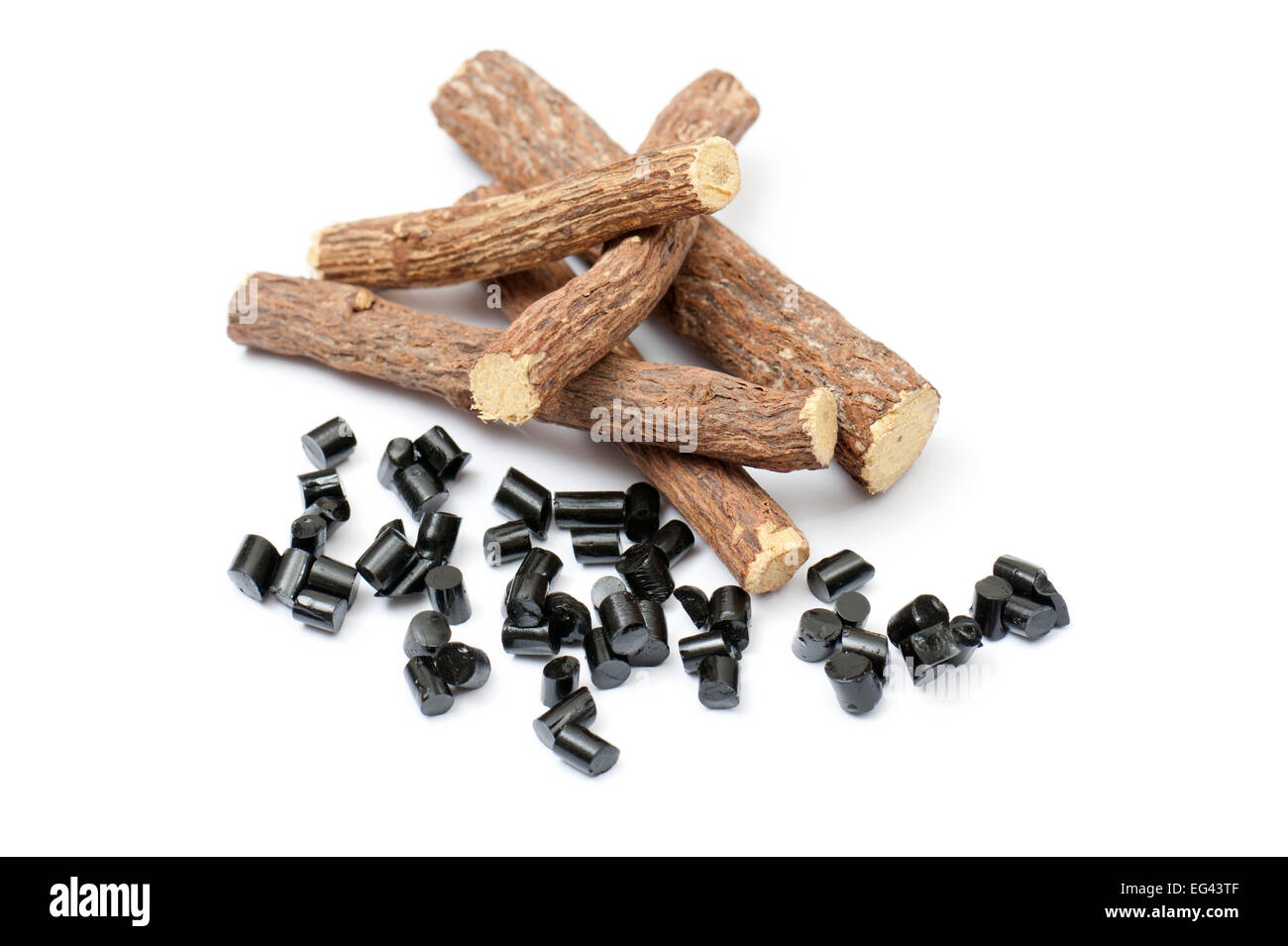 liquorice roots with black pieces, on white background - Stock Image