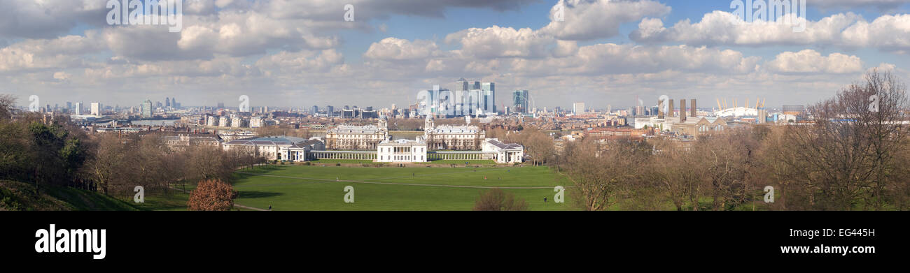 panoramic view over Greenwich Park in early spring with London skyline and docklands city beneath blue cloudy horizon - Stock Image
