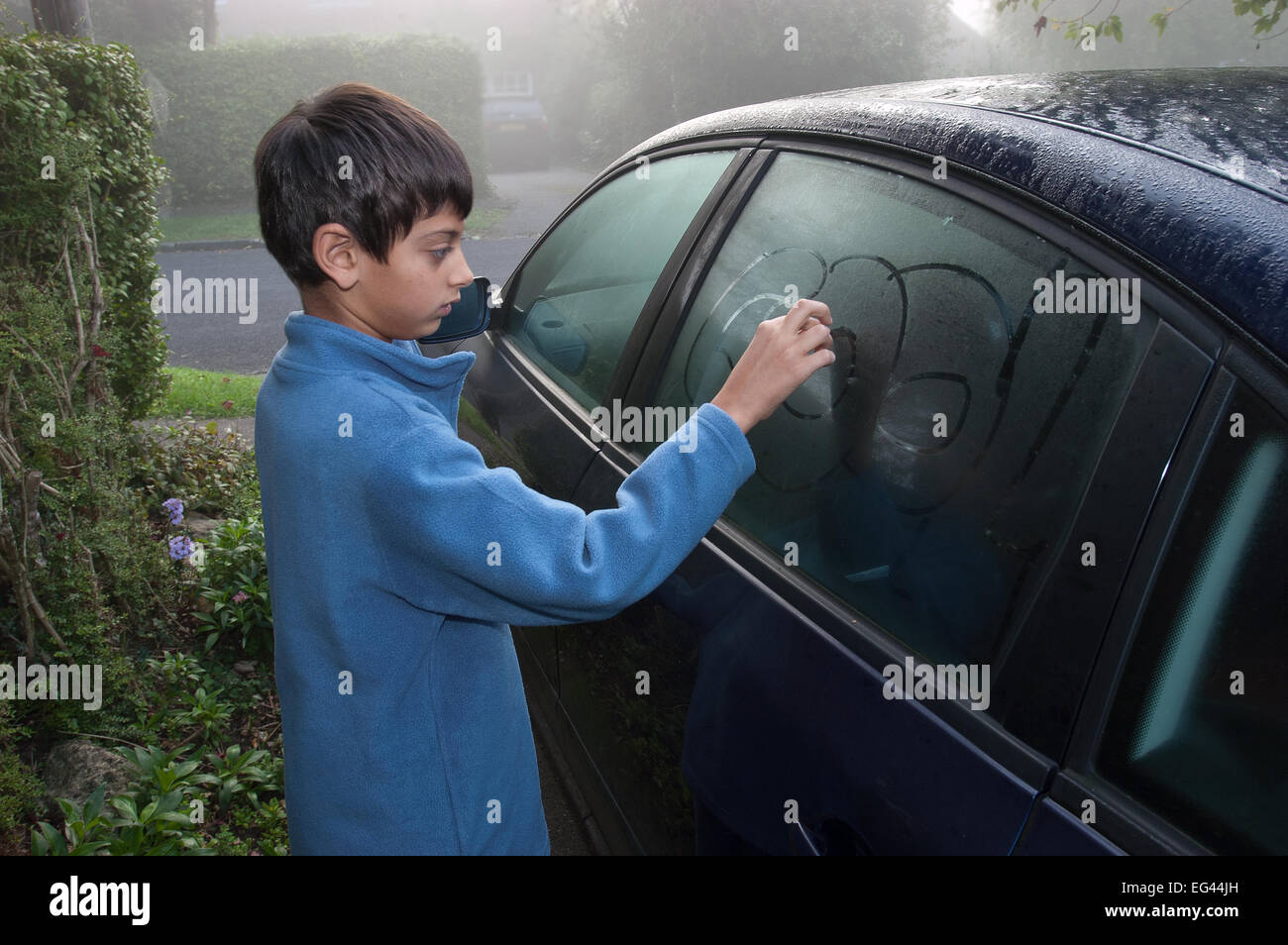 Young primary school boy drawing in and on car window on damp misty morning before school run - Stock Image