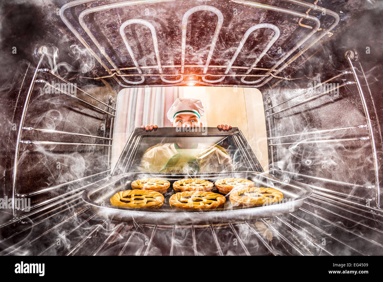 Funny chef overlooked pastries in the oven, so she had scorched, view from the inside of the oven. Cook perplexed - Stock Image