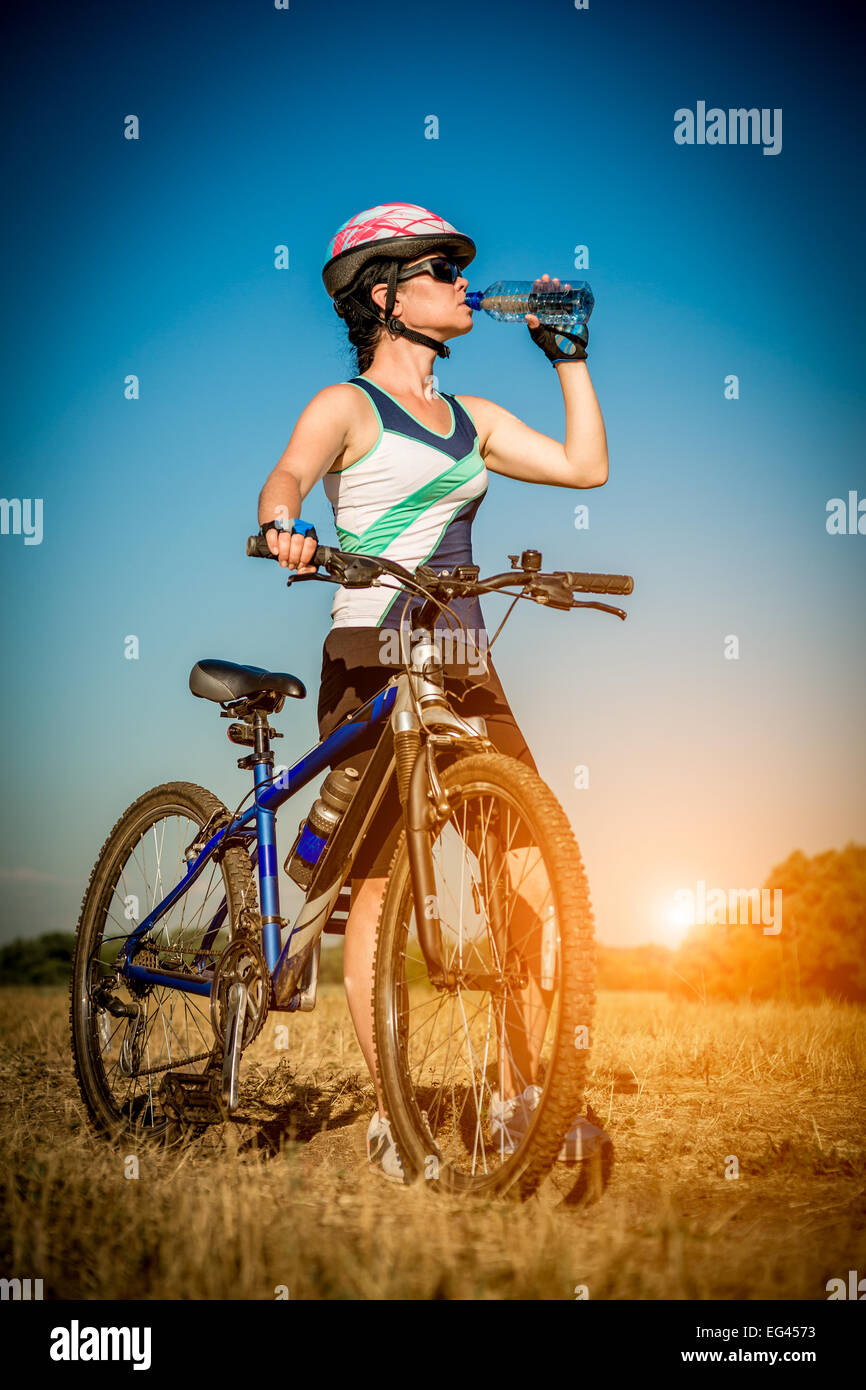 Woman with a bicycle drinking water from a bottle - Stock Image