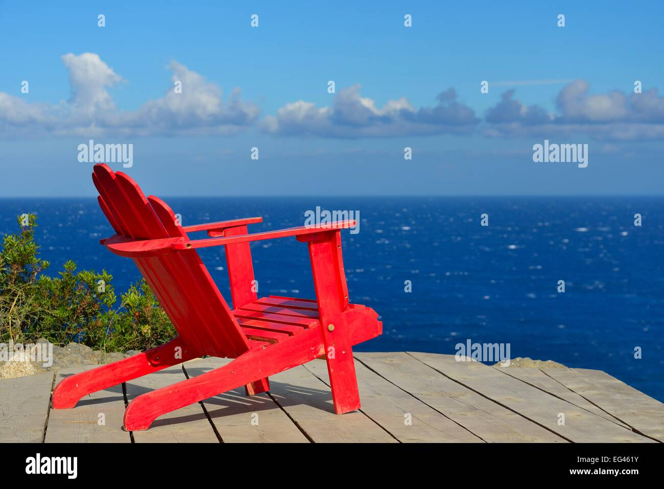 Red wooden chair on a terrace overlooking the Mediterranean Sea, Licciola in L'Ile-Rousse, Haute Corse, Corsica, - Stock Image
