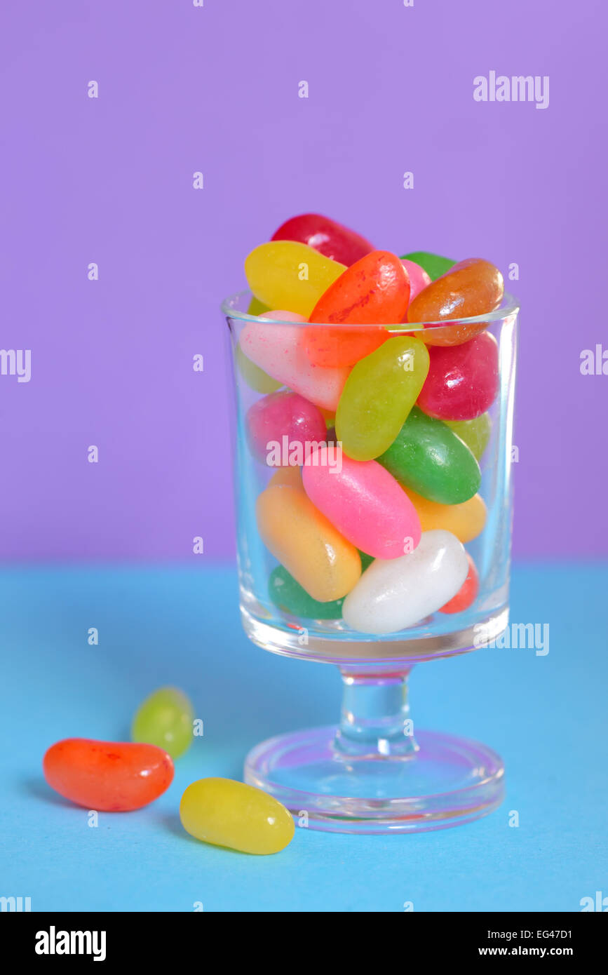 color Jelly Beans in glass on lila background - Stock Image