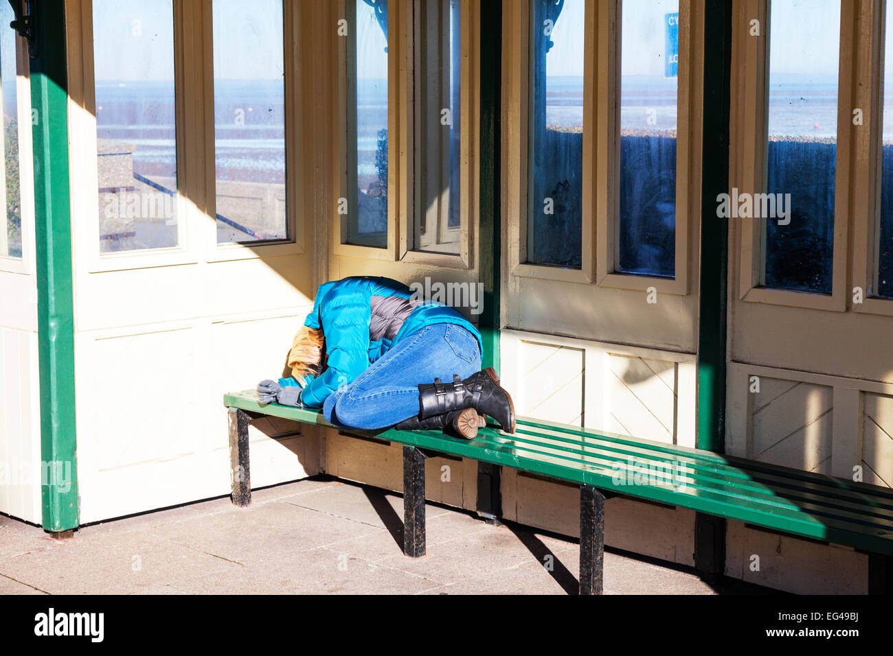 Girl sleeping rough vagrant tramp homeless person broken Britain desperate bus shelter Cleethorpes town lincolnshire - Stock Image
