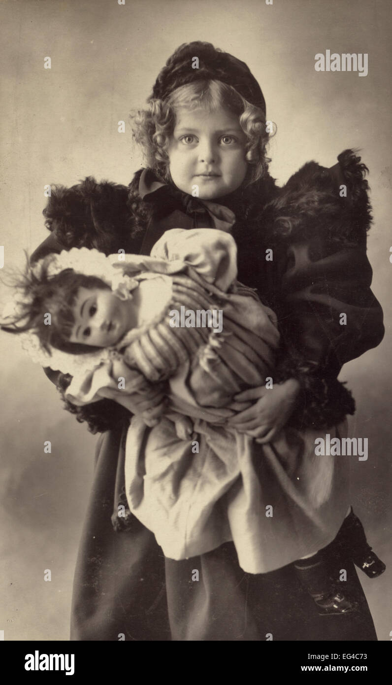 A young girl dressed in a fur-trimmed coat and hat, carrying her doll, circa 1898 - Stock Image