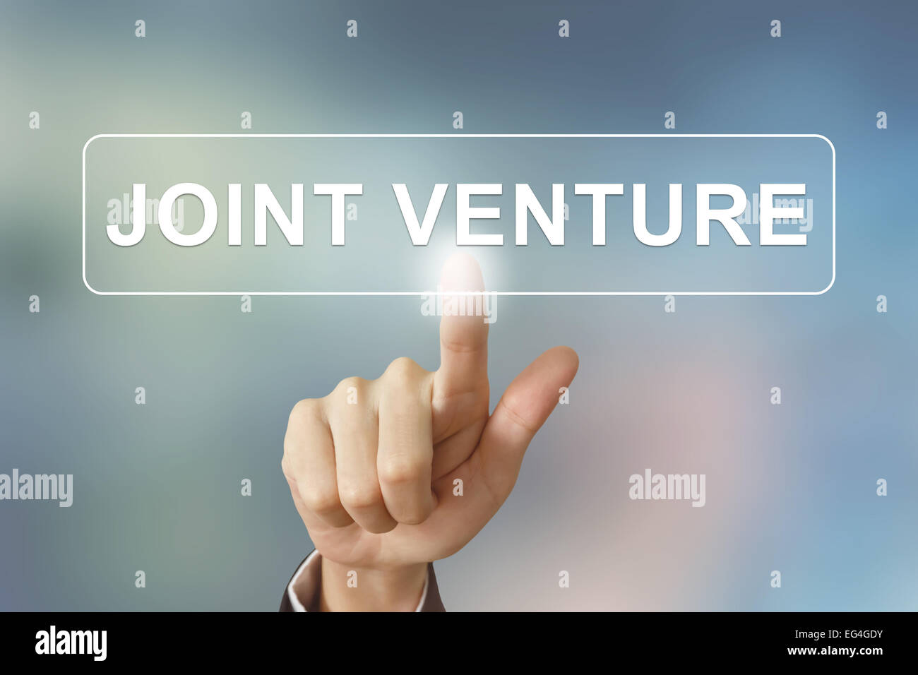 business hand pushing joint venture button on blurred background - Stock Image
