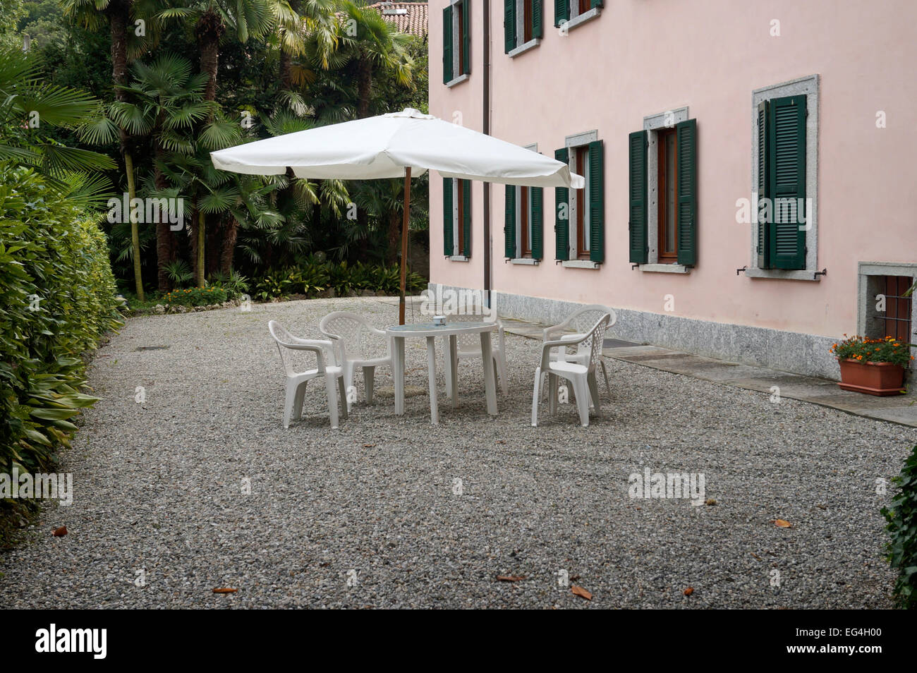 Secluded garden patio with garden table and chairs and sunshade umbrella - Stock Image