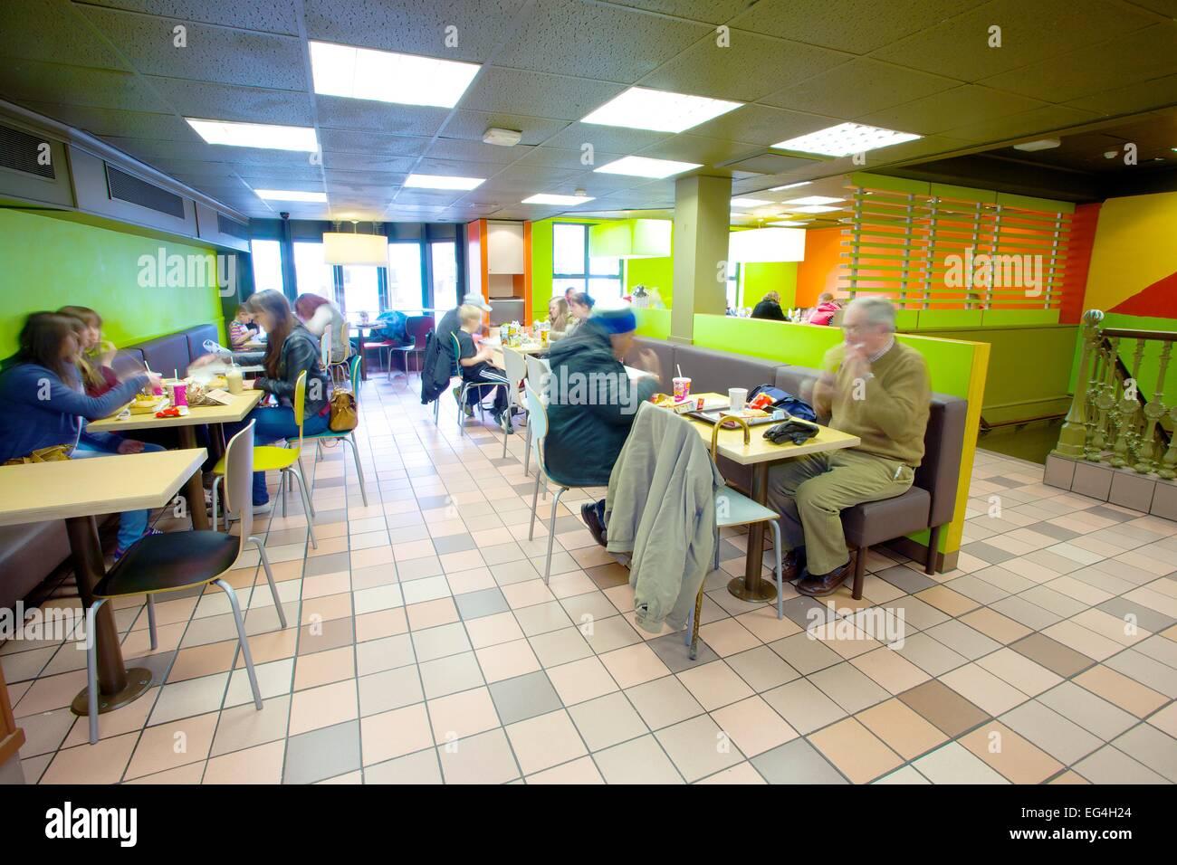 Customers Sitting Down In McDonalds Restaurant Interior.