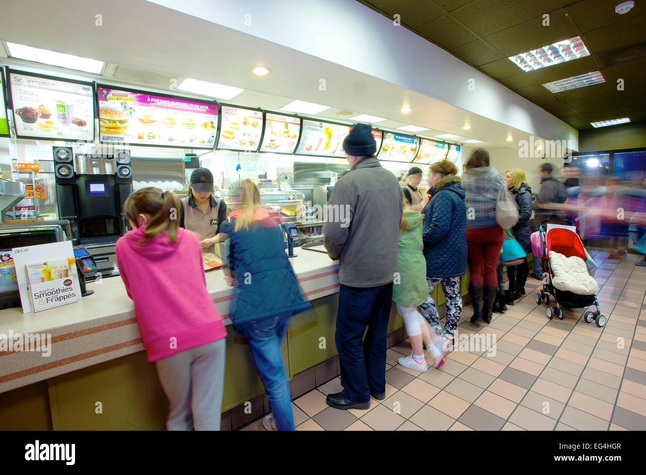 Customers at counter. McDonalds restaurant interior. - Stock Image