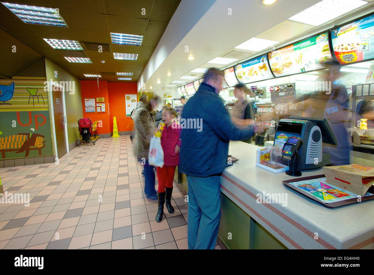 Customers at counter. McDonalds restaurant interior. - Stock Image
