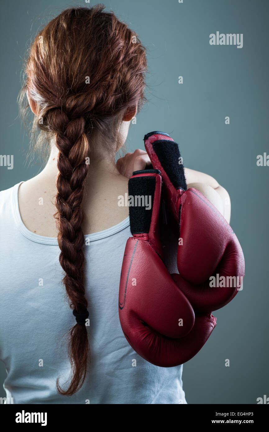 Woman with Braid Holding Two Boxing Gloves - Stock Image