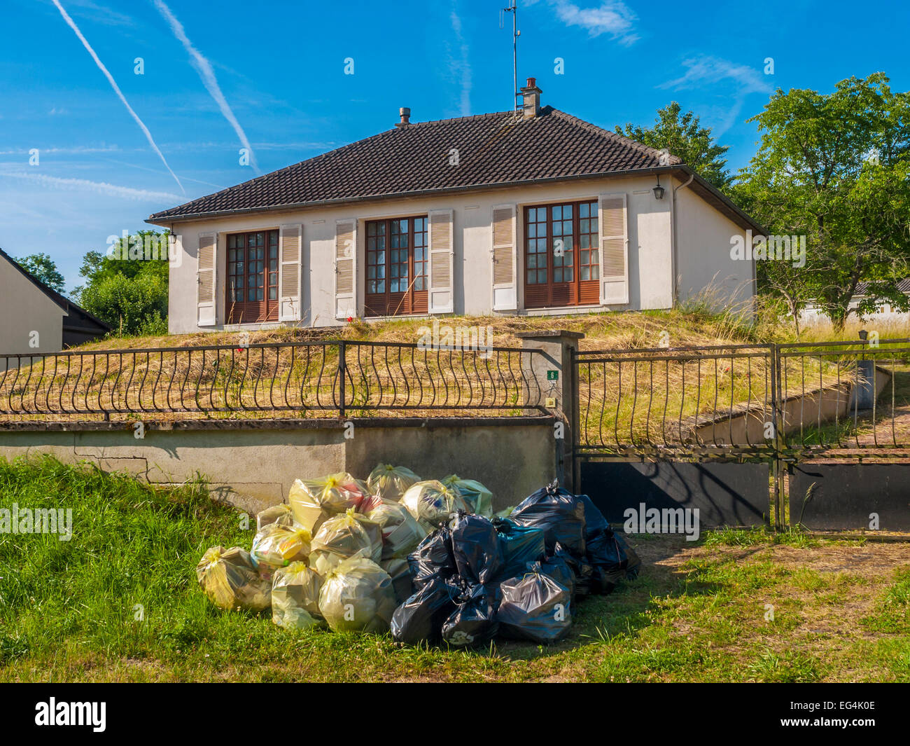 Many plastic sacks of household rubbish outside bungalow awaiting collection - France. - Stock Image