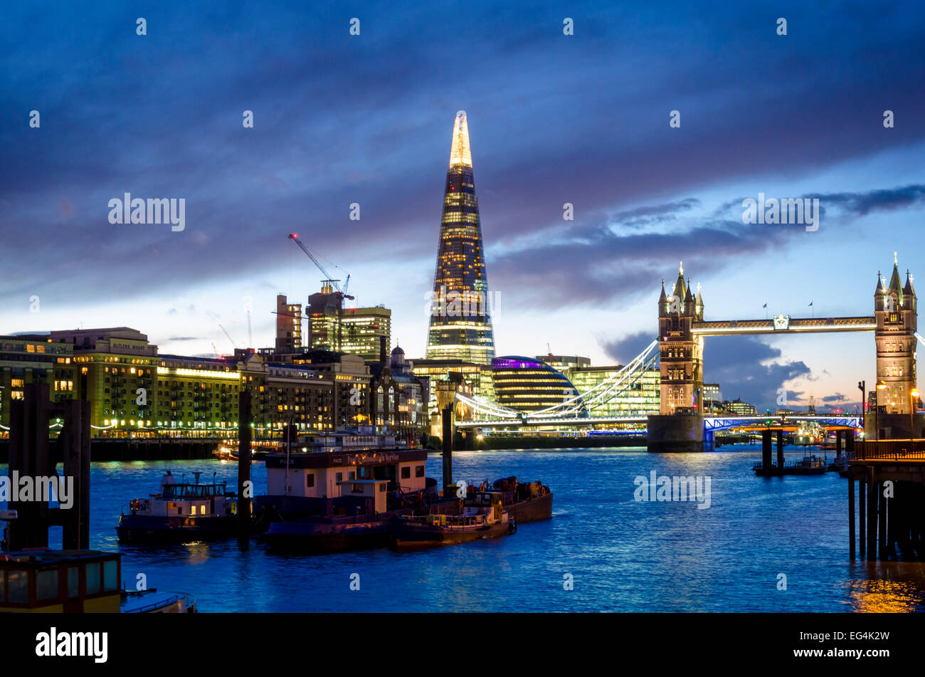 Tower Bridge and The Shard viewed from the north bank of the Thames at night. London, UK - Stock Image