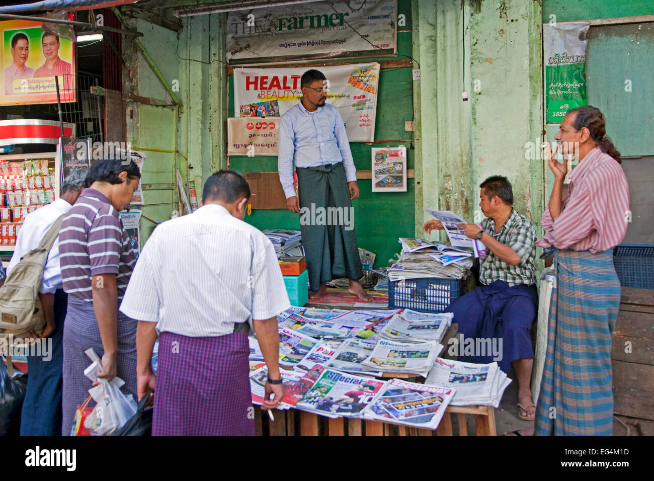 Burmese men buying daily newspapers and journals at street stall in Yangon / Rangoon, former capital city of  Myanmar Stock Photo