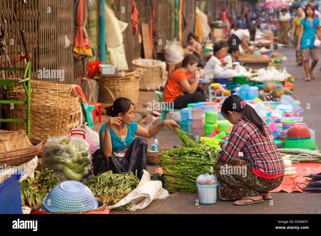 Burmese female street vendors selling food and goods on the ground at market in Yangon / Rangoon, Myanmar / Burma - Stock Image