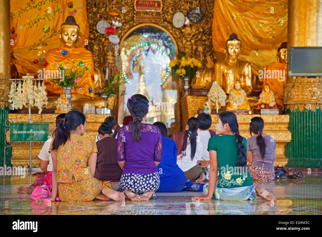 Burmese women praying barefooted in the Shwedagon Zedi Daw Pagoda at Yangon / Rangoon, former capital city of  Myanmar - Stock Image